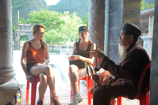 Old artist plays traditional instrument to foreign visitors