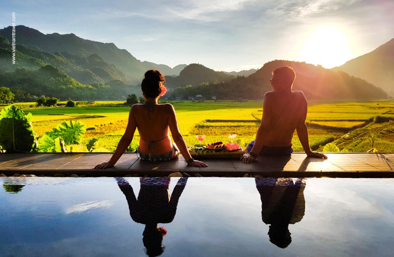 Tourists relaxing on swimming pool with panorama view to rice fields in Mai Chau