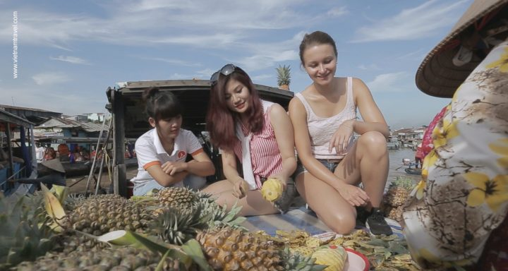 Tourists trying local fruits on a boat in Cai Rang floating market, Can Tho