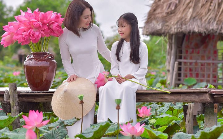Beautiful mother and daughter in white Ao Dai pose in lotus pond.