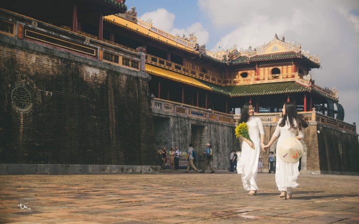 Vietnamese girls wearing Ao Dai and taking photos in front of Imperial City of Hue