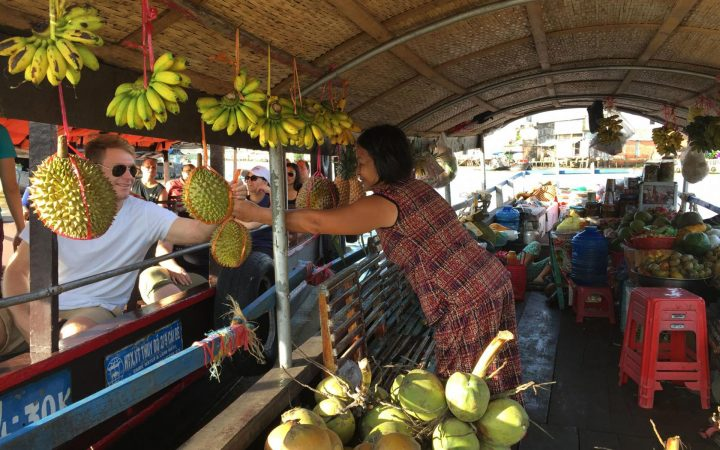 Tourists buying some fruits from a boat on Cai Be floating market