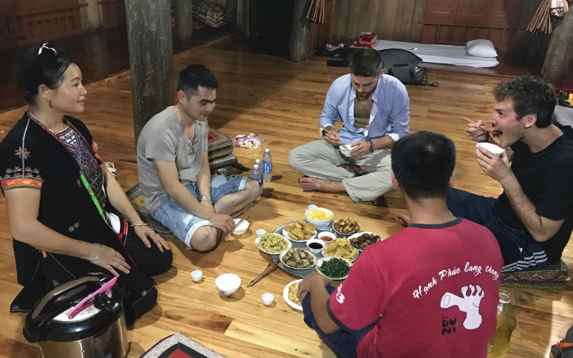 Tourists enjoy traditional dinner with ethnic people in Ngoi Tu Cultural Village.