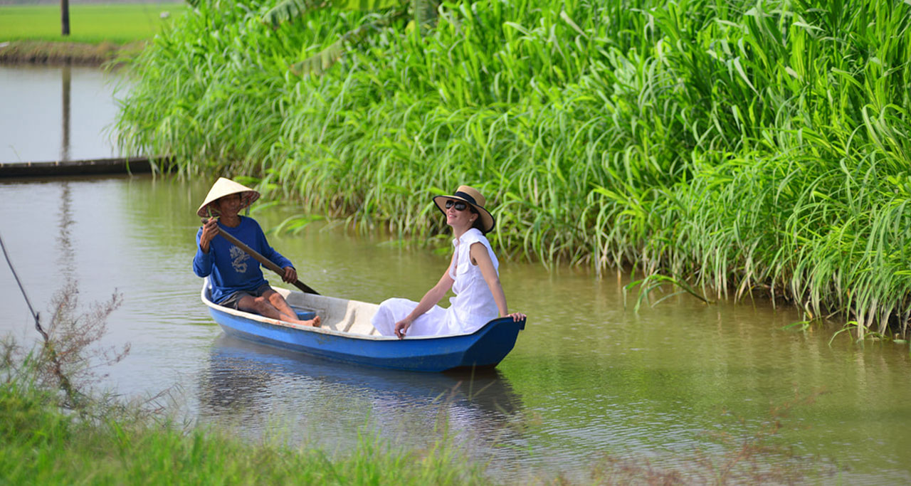 A foreign tourist take a traditional sampan to explore Mekong Delta region