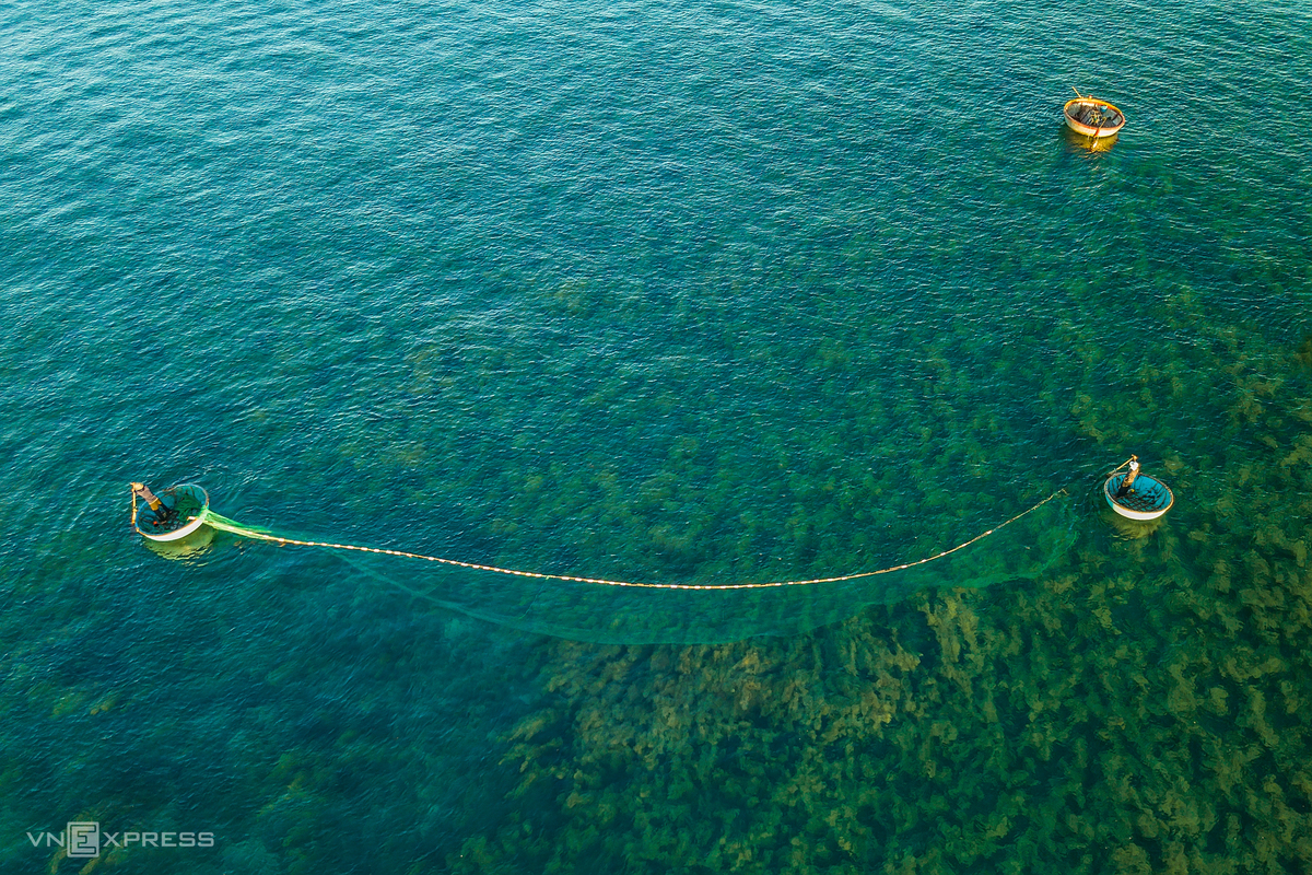 A couple putting fishing net into the sea in Quang Ngai